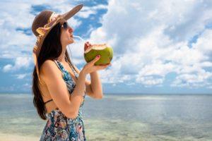 Frau trinkt Kokoswasser mit Strohhalm aus Kokosnuss