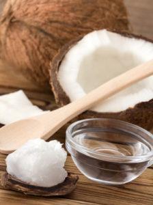 Kokosöl in Schale auf Tisch mit offener Kokosnuss