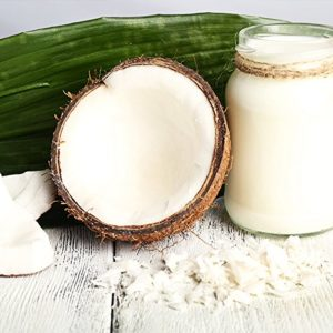 Kokosfett im Glas mit aufgebrochnerner Kokosnuss und Kkoksblatt auf weissem Boden